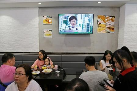 People sit at a restaurant as a news conference of Hong Kong Chief Executive Carrie Lam is broadcasted in TV in Hong Kong