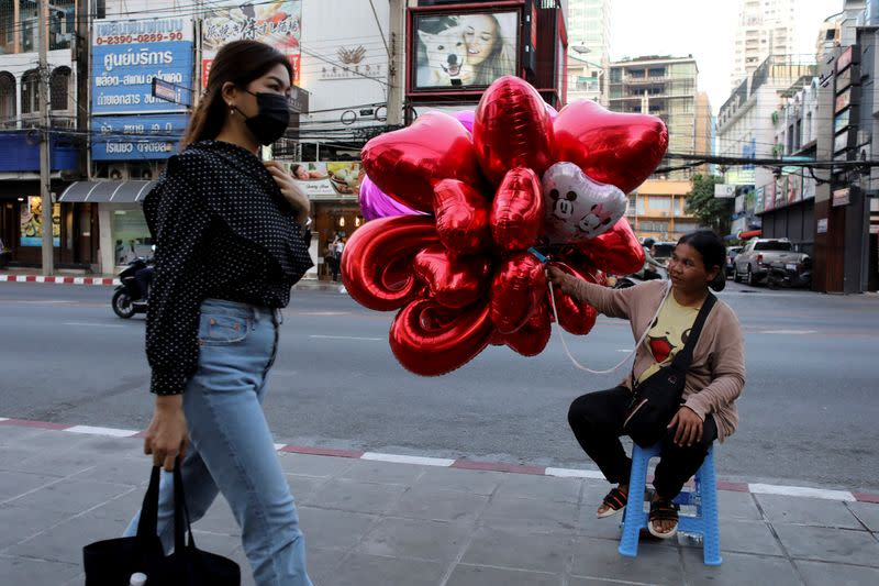 A woman wearing protective walks past a woman selling ballons to celebrate Valentine's Day in Bangkok