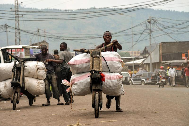 Men transport goods on tshukudus, wooden push-bikes, in Goma on June 18, 2014 (AFP Photo/Junior D. Kannah)