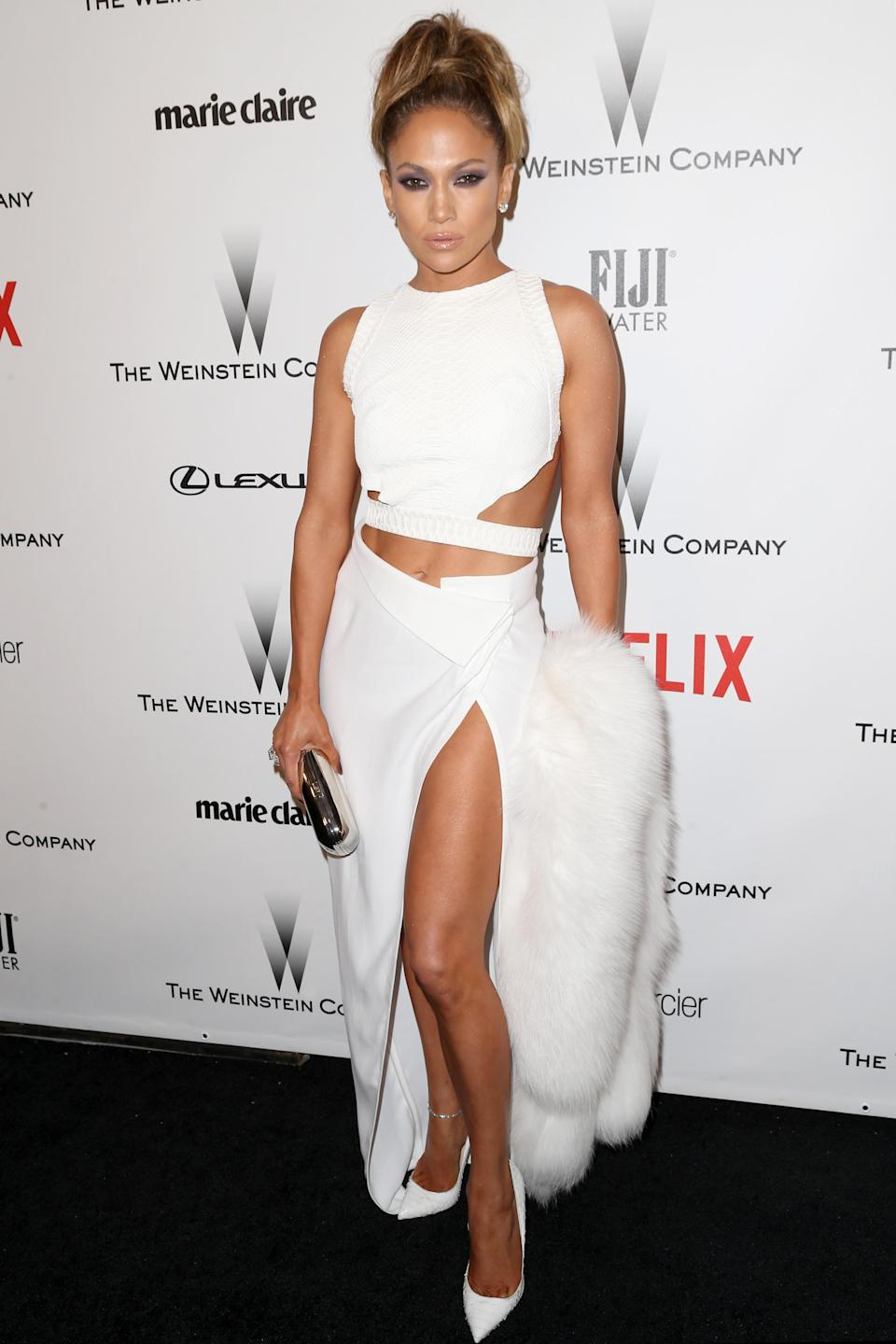 <p>Sporting a higher neckline, the performer still managed to flaunt her flawless abs in a high-slit, all-white two piece. [Photo: Getty] </p>