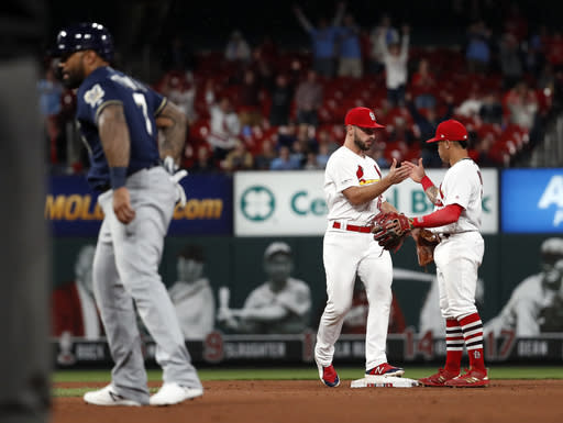 St. Louis Cardinals' Paul DeJong and Kolten Wong, right, celebrate as Milwaukee Brewers' Eric Thames, left, heads off the field following a baseball game Tuesday, April 23, 2019, in St. Louis. The Cardinals won 4-3. (AP Photo/Jeff Roberson)