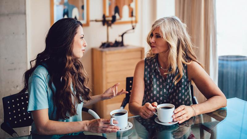 Older mother and daughter spending time together at home drinking coffee and discussing.