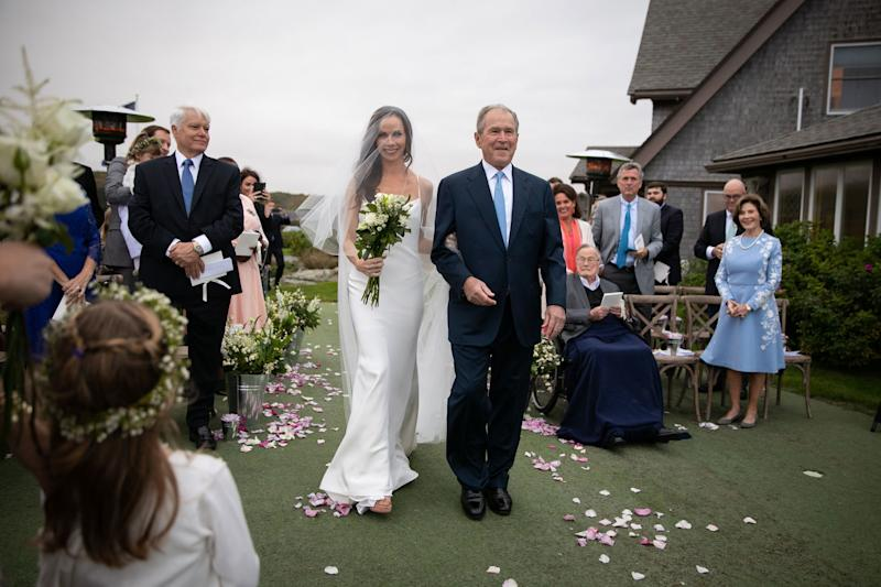The bride, wearing custom Vera Wang, makes her way down the aisle escorted by her father, former President George W. Bush, while her grandfather and mother look on.