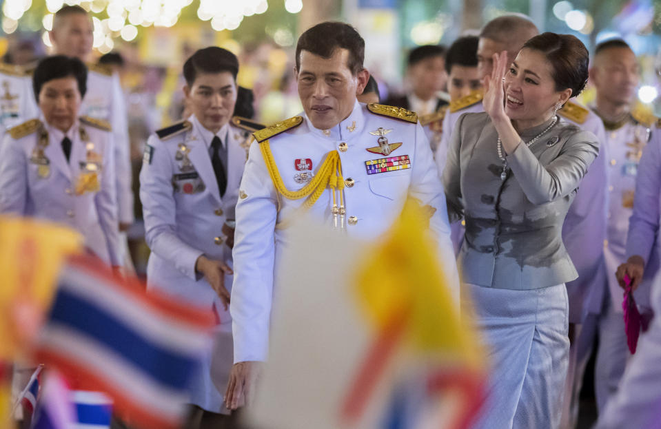 King Maha Vajiralongkorn, center left and Queen Suthida, center right wave to supporters in Bangkok, Thailand, Sunday, Nov. 1, 2020. Under increasing pressure from protesters demanding reforms to the monarchy, Thailand's king and queen met Sunday with thousands of adoring supporters in Bangkok, mixing with citizens in the street after attending a religious ceremony inside the Grand Palace. (AP Photo/Wason Wanichakorn)