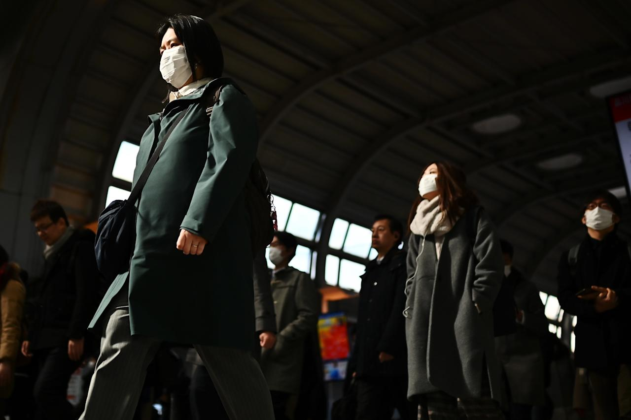 Mask-clad commuters make their way to work during morning rush hour at the Shinagawa train station in Tokyo on February 28, 2020. - Tokyo's key Nikkei index plunged nearly three percent at the open on February 28 after US and European sell-offs with investors worried about the economic impact of the coronavirus outbreak. (Photo by CHARLY TRIBALLEAU / AFP) (Photo by CHARLY TRIBALLEAU/AFP via Getty Images)