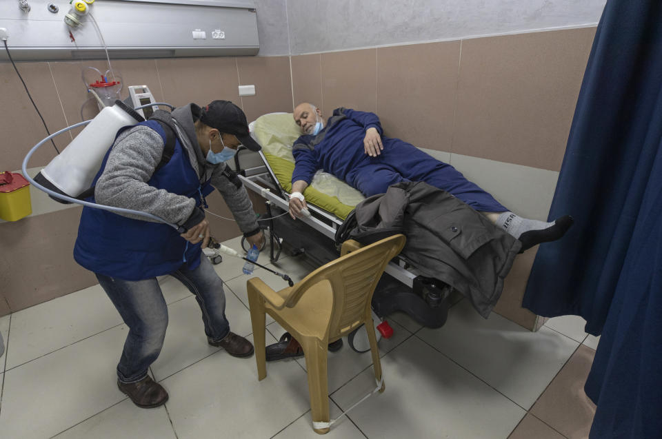 A Palestinian medical staffer sterilizes a room occupied by a COVID-19 patient who is under medical observation, at the emergency unit, of the Palestine Medical Complex, in the West Bank city of Ramallah, Tuesday, March 2, 2021. (AP Photo/Nasser Nasser)