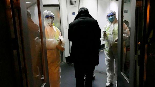 PHOTO: Health Officials in hazmat suits wait at the gate to check body temperatures of passengers arriving from the city of Wuhan Wednesday, Jan. 22, 2020, at the airport in Beijing, China. (Emily Wang/AP)