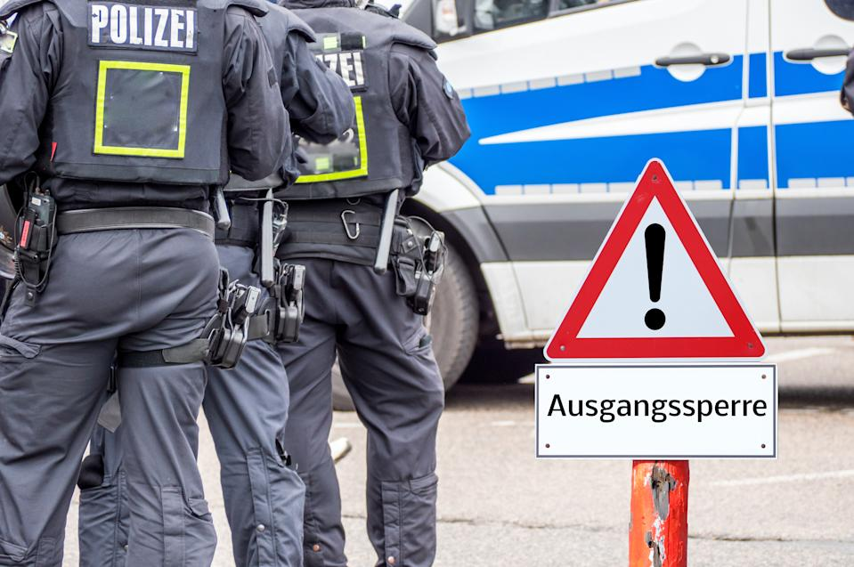 Police curfew warning sign in german background