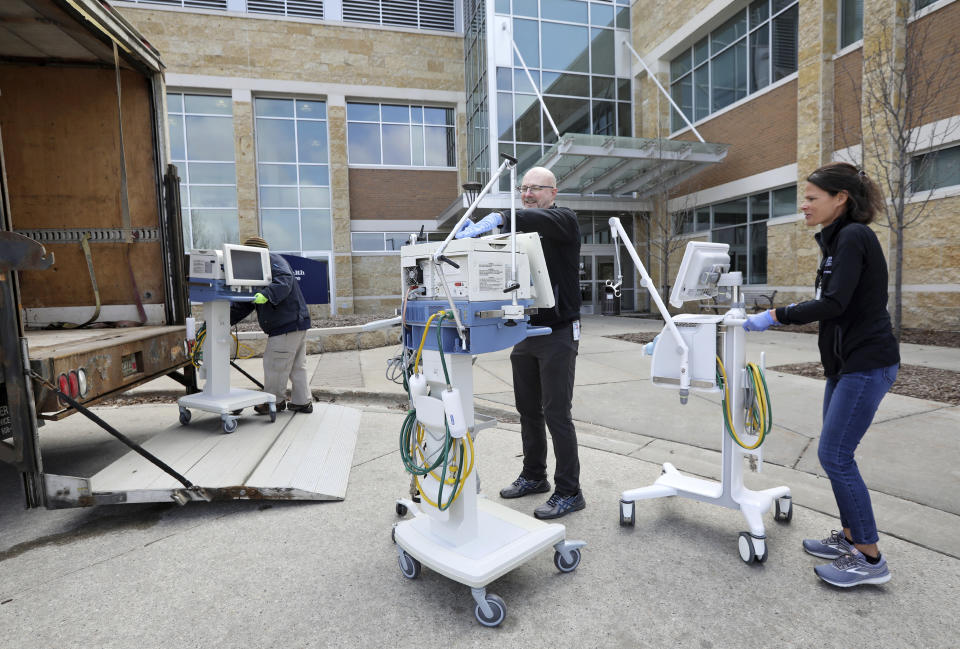 Amy Setchell, at right, program director of the respiratory therapy program at Madison Area Technical College, and Chris Becker, director of clinical education of the respiratory therapy program at MATC, load ventilators, that the school is lending  due to coronavirus to SSM Health, along with other area hospitals, into a truck outside the college's Health Education Building in Madison, Wis., Tuesday, March 24, 2020. (Amber Arnold/Wisconsin State Journal via AP)