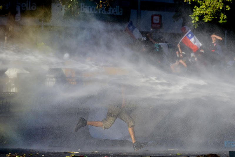 An anti-government runs through spray coming from a police water cannon during clashes in Santiago, Chile, Monday, Oct. 28, 2019. Fresh protests and attacks on businesses erupted in Chile Monday despite President Sebastián Piñera's replacement of eight important Cabinet ministers with more centrist figures, and his attempts to assure the country that he had heard calls for greater equality and improved social services. (AP Photo/Matias Delacroix)