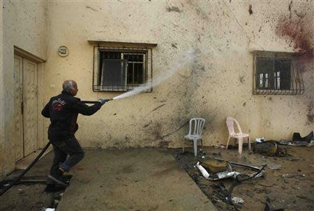 A Palestinian man hoses blood from the wall of a house at the scene of an Israeli air strike in Beit Hanoun, in Gaza
