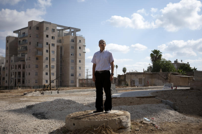 "In this photo taken on Thursday, Sept. 20, 2012, Israeli Jewish activist Aharon Attias poses for a photograph in front of new housing project for religious Jews in Israel's mixed Arab-Jewish town of Lod, central Israel. Religious Jews who are the bedrock of the settlement movement have marked Israel's mixed Arab-Jewish cities as the new front to ""reclaim,"" pushing into Arab neighborhoods to cement the Jewish presence there. The migration of several thousand devout Jews to rundown areas of Jaffa, Lod, Ramle and Acco has had a divisive effect far outweighing their absolute numbers, with Jews celebrating _ and Arab activists eyeing with mistrust and resentment _ the construction of Jewish seminaries and housing developments marketed exclusively to Jews. (AP Photo/Ariel Schalit)"