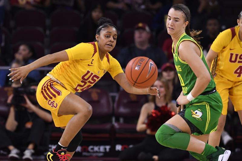 Southern California guard Desiree Caldwell left, and Oregon guard Sabrina Ionescu go after a loose ball during the first half of an NCAA college basketball game Sunday, Feb. 16, 2020, in Los Angeles. (AP Photo/Mark J. Terrill)