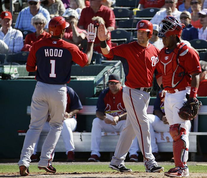 Washington Nationals' Destin Hood, left, high-fives teammate Jason Martinson, center, after Hood hit a three-run home run to score Martinson and Mike Fontenot in the eighth inning of an exhibition spring training baseball game against the St. Louis Cardinals, Saturday, March 8, 2014, in Jupiter, Fla. (AP Photo/David Goldman)