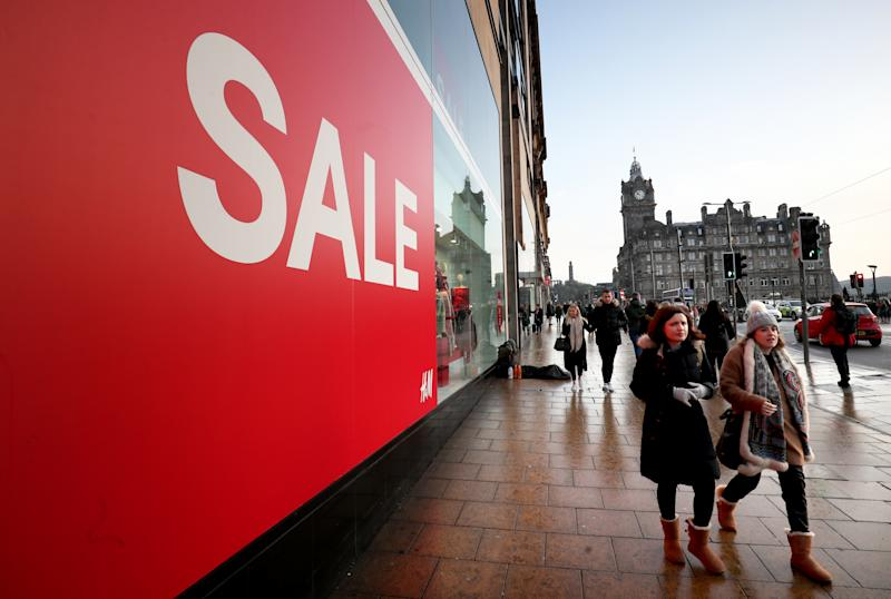 Shoppers pass a sale sign in the window of H&M on Princes Street, Edinburgh, during the Boxing Day sales.