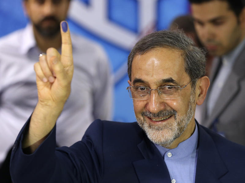 In this photo taken on Saturday, May 11, 2013, conservative former Iranian Foreign Minister, Ali Akbar Velayati, a senior advisor to supreme leader Ayatollah Ali Khamenei, shows his inked finger to media as he registers his candidacy for the upcoming presidential election, at the election headquarters of the interior ministry in Tehran, Iran. He was selected Tuesday, May 21, 2013 as one of eight candidates allowed to push ahead with his presidential bid. Velayati, 67, served as foreign minister during the 1980-88 war with Iraq and into the 1990s. He is a physician and runs a hospital in north Tehran. He was among the suspects named by Argentina in a 1994 bombing of a Jewish center in Buenos Aires that killed 85 people. (AP Photo/Ebrahim Noroozi)