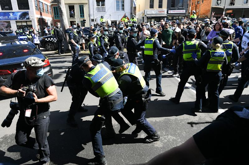 Picture of a police scuffle as they cashed with protesters in Melbourne