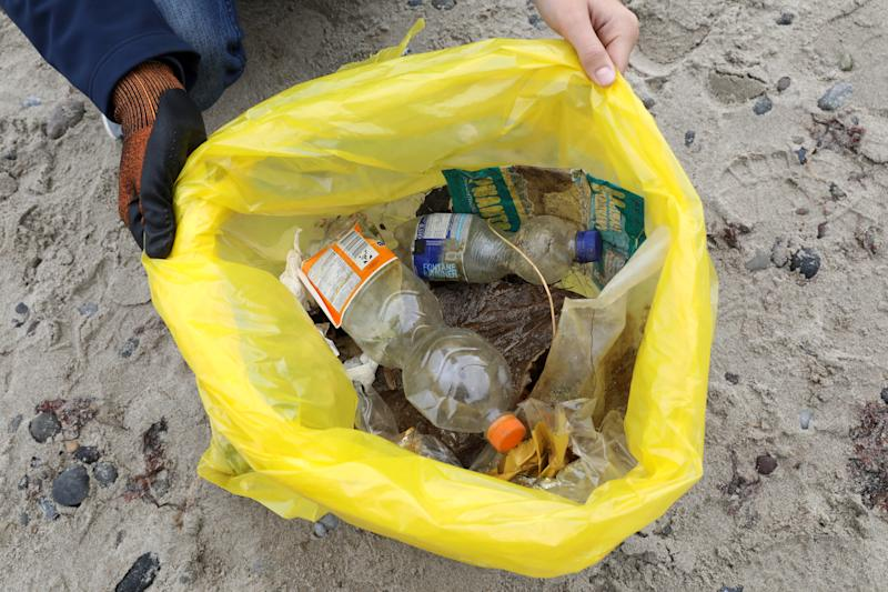 "21 September 2019, Mecklenburg-Western Pomerania, Rostock: A participant of the ""Coastal Cleanup Day"" shows the contents of his filled garbage bag at the Baltic Sea beach of Diedrichshagen. Environmental associations have called for the waste collection campaign. Throughout the world, up to 13 million tons of plastic waste were transported from land to sea every year. The ""Coastal Cleanup Day"" is intended to help remove the garbage, but also to draw attention to the problems themselves. Photo: Bernd Wüstneck/dpa-Zentralbild/dpa (Photo by Bernd Wüstneck/picture alliance via Getty Images)"