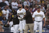 San Diego Padres' Fernando Tatis Jr., center, is helped off the field by manager Jayce Tingler, left, and a trainer during the first inning the team's baseball game against the Colorado Rockies, Friday, July 30, 2021, in San Diego. (AP Photo/Derrick Tuskan)