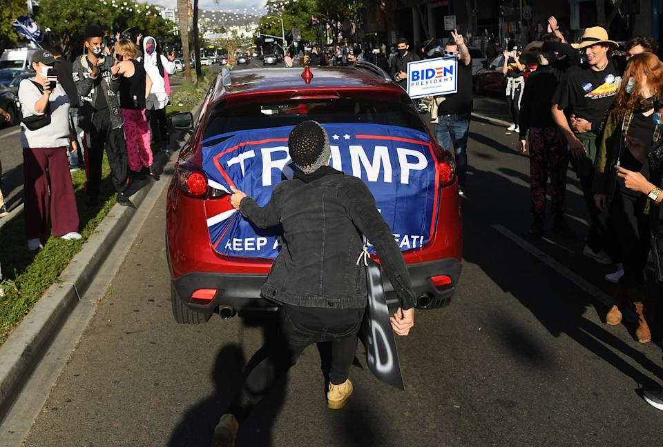 A Trump flag is ripped off a car in West Hollywood.