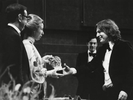 Parker (right) collects his Bafta in 1977 (Rex)