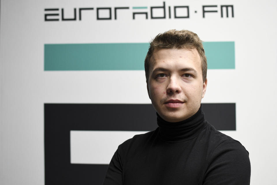 FILE - In this Nov. 17, 2019, file photo, provided by European Radio for Belarus, dissident journalist Raman Pratasevich poses for a photo in front of euroradio.fm sign in Minsk, Belarus. Pratasevich and another young journalist, Stsiapan Putsila, set up a channel on the Telegram messaging app called Nexta, which was used to organize demonstrations against authoritarian President Alexander Lukashenko. (Euroradio via AP, File)