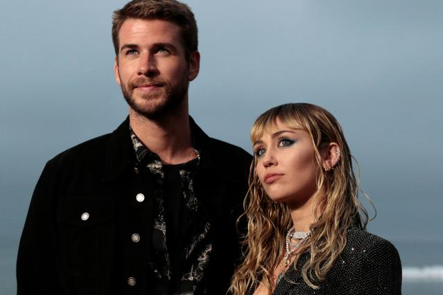 Miley Cyrus and Liam Hemsworth arrive for the Saint Laurent Men's Spring-Summer 2020 runway show. (Photo by Kyle GRILLOT / AFP)