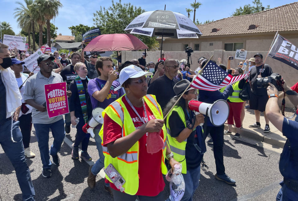 Demonstrators march toward the office of U.S. Sen. Kyrsten Sinema, D-Arizona, on Monday, July 26, 2021, in Phoenix. Thirty-five people were arrested, including civil rights leader Rev. Jesse Jackson, for refusing to leave Sinema's office while protesting her opposition to ending the filibuster to pass voting rights legislation. (AP Photo/Jonathan J. Cooper)