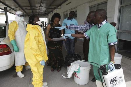 A health worker sprays a colleague with disinfectant during a training session for Congolese health workers to deal with Ebola virus in Kinshasa