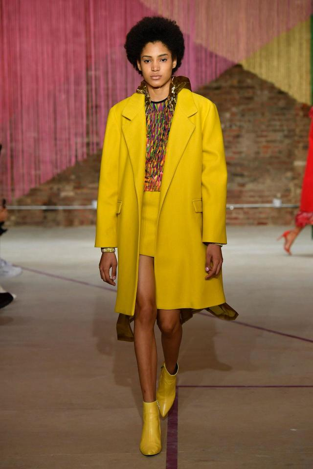 <p>Model wears a canary yellow coat, skirt, boots and multicolor top at the Milly Fall/Winter 2018 show. (Photo: Courtesy of Greg Kessler) </p>