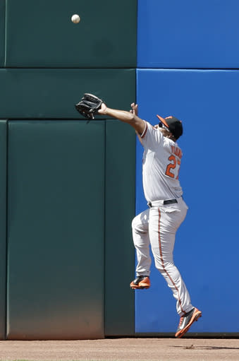 Baltimore Orioles' Delmon Young leaps to catch a ball hit by Cleveland Indians' Lonnie Chisenhall in the fourth inning of a baseball game, Sunday, Aug. 17, 2014, in Cleveland. Chisenhall was out on the play. (AP Photo/Tony Dejak)