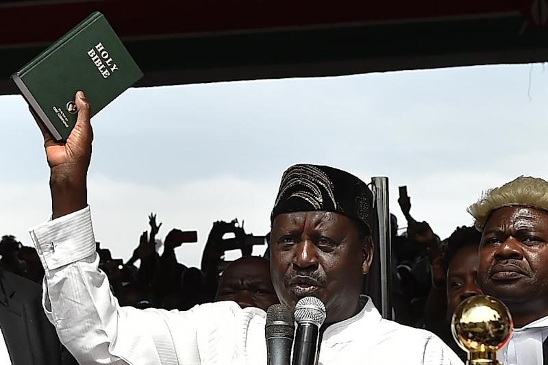 Kenya's opposition leader Raila Odinga (L) holds up a bible as he swears himself in as the 'people's president' in Nairobi