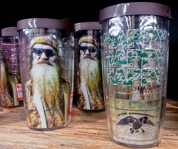 """This Saturday, Dec. 21, 2013 photo shows items showing the image of Phil Robertson and his catchphrase """"Happy, Happy, Happy"""" displayed at the Duck Commander store in West Monroe, La. The town is the setting for the popular """"Duck Dynasty""""series, where show patriarch, Phil Robertson, was suspended last week for disparaging comments he made to GQ magazine about gay people. (AP Photo/Matthew Hinton)"""