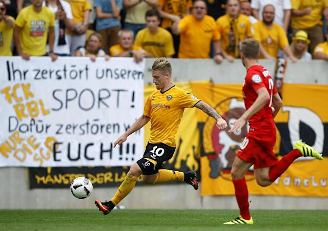 "Football Soccer - Dynamo Dresden v RB Leipzig - German Cup (DFB Pokal) - DDV-Stadion, Dresden, Germany - 20/08/16. Dynamo Dresden's Marvin Stefaniak (L) in action with RB Leipzig's Benno Schmitz. Banner displayed by Dynamo Dresden's fans rads: ""You destroy our sport ! For this we will destroy you !!!"" REUTERS/Axel Schmidt. DFB RULES PROHIBIT USE IN MMS SERVICES VIA HANDHELD DEVICES UNTIL TWO HOURS AFTER A MATCH AND ANY USAGE ON INTERNET OR ONLINE MEDIA SIMULATING VIDEO FOOTAGE DURING THE MATCH."