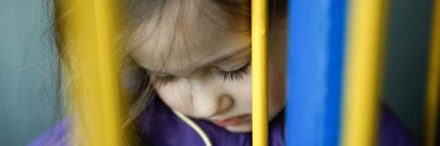 A young girl looking down behind a colorful fence