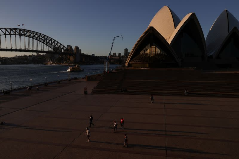 People are seen in front of the Sydney Opera House and Sydney Harbour Bridge in Sydney