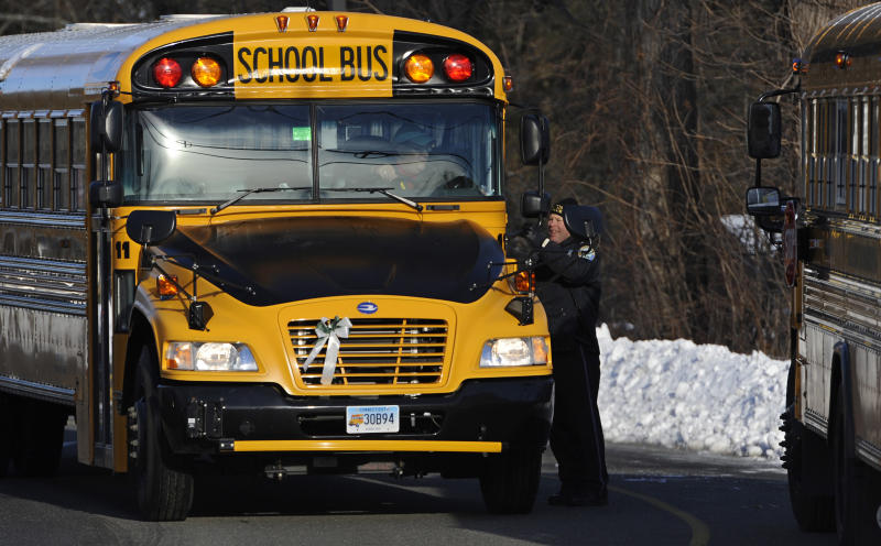 A police officer greets a bus at the entrance to a school on the first day of classes after the holiday break, in Newtown, Conn., Wednesday, Jan. 2, 2013. Nearly three weeks after the shooting rampage at Sandy Hook Elementary School in Newtown, students and teachers from the school will return to class Thursday in the neighboring town of Monroe. (AP Photo/Jessica Hill)