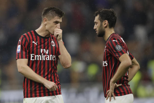 AC Milan's Krzysztof Piatek, left, and AC Milan's Hakan Calhanoglu react at the end of Serie A soccer match between AC Milan and Lecce, at the San Siro stadium in Milan, Italy, Sunday, Oct.20, 2019. (AP Photo/Luca Bruno)