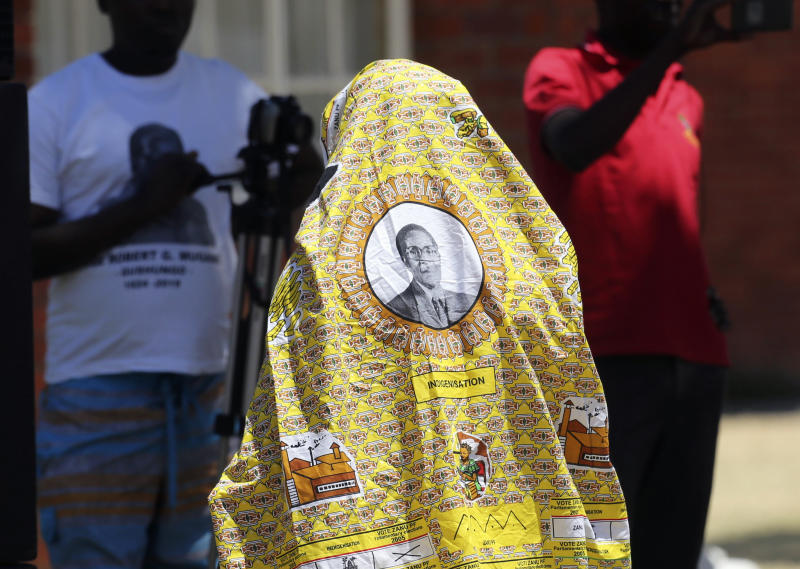 A man covers himself with a cloth bearing the portrait of former Zimbabwean President Robert Mugabe at his rural home in Zvimba, about 100 kilometer north west of the capital Harare, Saturday, Sept. 28, 2019. According to a family spokesperson Mugabe is expected to be buried at the residence after weeks of drama mystery and contention over his burial place.(AP Photo/Tsvangirayi Mukwazhi)