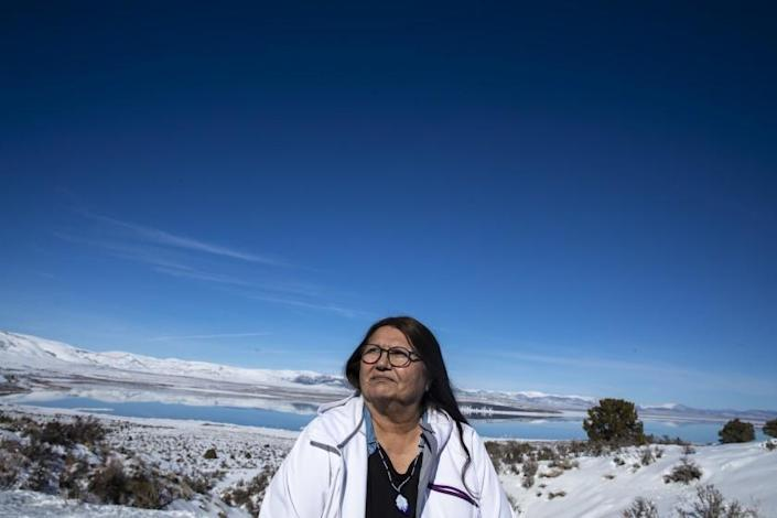"""LEE VINING, CA - FEBRUARY 04: Charlotte Lange, 67, chairwoman of the Mono Lake Kutzadika Paiute Tribe, sits for a portrait on a bluff overlooking Mono Lake on Thursday, Feb. 4, 2021 in Lee Vining, CA. The tribe is among roughly two dozen unrecognized and landless tribes in California. Lange said, """"We just want a place to call home, and time is running out."""" (Brian van der Brug / Los Angeles Times)"""