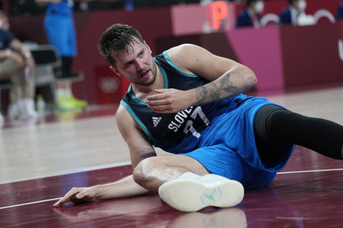 Slovenia's Luka Doncic (77) lays on the floor after he was knocked down on a play during a men's basketball semifinal round game against France at the 2020 Summer Olympics, Thursday, Aug. 5, 2021, in Saitama, Japan. (AP Photo/Eric Gay)