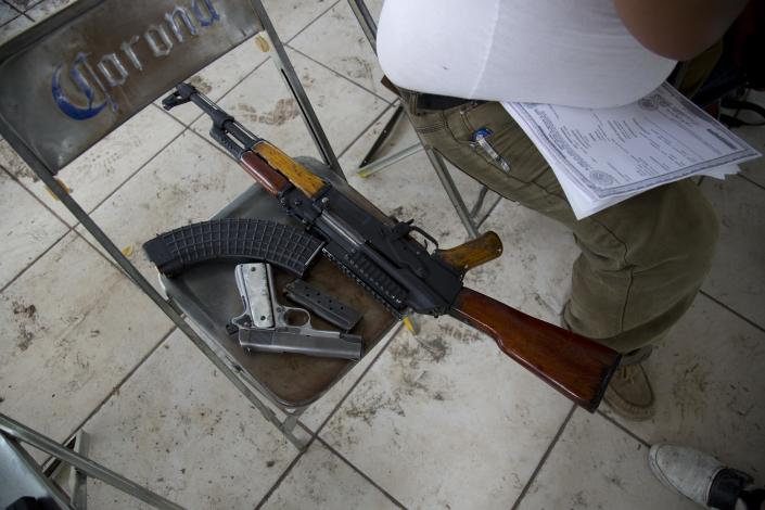 A member of a self-defense group sits next his weapons as he waits to register his weapons in Apatzingan, Mexico, Thursday, May 8, 2014. The confusing proliferation of false self-defense groups in Michoacan and instances of alleged looting and killings by legitimate vigilantes have led the federal government to tell the vigilantes they have to demobilize by May 10. (AP Photo/Eduardo Verdugo)