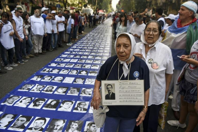 Members of the Madres de Plaza de Mayo and Abuelas de Plaza de Mayo human rights organizations and thousands of demonstrators stand by a large banner with portraits of people who disappeared during the 1976-1983 military dictatorship, in Buenos Aires