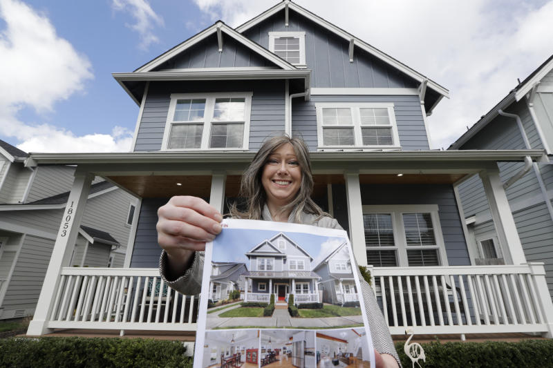 In this Wednesday, April 1, 2020 photo, Rebeka McBride holds a picture of her home as she poses in front of it in Monroe, Wash., outside of Seattle. She put her house on the market in early March and is in the process of closing on the sale. (AP Photo/Elaine Thompson)