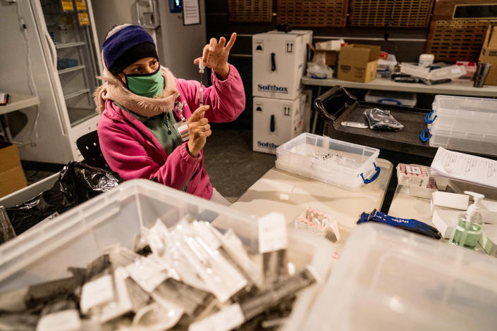 Bernie Delgado prepares doses of the Pfizer-BioNTech vaccine in a cold storage room set up at Pratt & Whitney Stadium in East Harford, Conn., Feb. 4, 2021. (Christopher Capozziello/The New York Times)