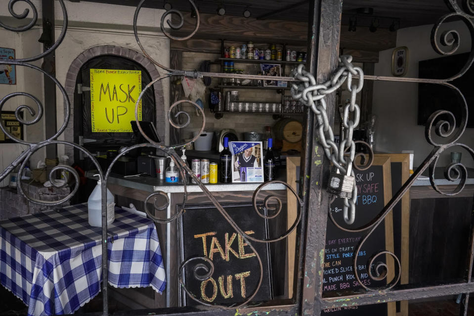 The doors of the Baby Blues BBQ restaurant are seen locked in Los Angeles Monday, Jan. 25, 2021. California has lifted regional stay-at-home orders statewide in response to improving coronavirus conditions. Public health officials said Monday that the state will return to a system of county-by-county restrictions intended to stem the spread of the virus. Local officials could choose to continue stricter rules. The state is also lifting a 10 p.m. to 5 a.m. curfew. (AP Photo/Damian Dovarganes)