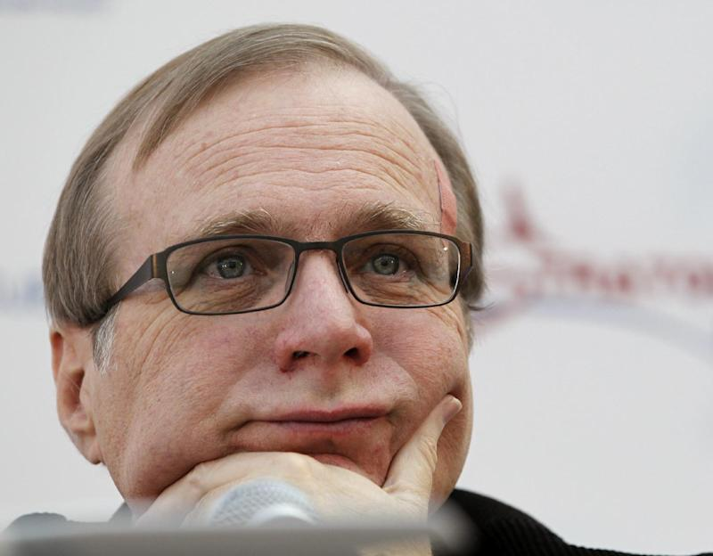 FILE - In this Dec. 13, 2011 photo, Microsoft co-founder Paul Allen listens during a a news conference in Seattle.   An AWOL soldier's simple scheme to defraud one of the richest men in the world has landed him in federal custody, according to a criminal complaint. In the complaint unsealed Monday, March 26, 2012, federal investigators allege Brandon Lee Price changed the address on a bank account held by billionaire Microsoft co-founder Paul Allen, then had a debit card sent to his Pittsburgh home so he could use it for payments on a delinquent Armed Forces Bank account and personal expenses. (AP Photo/Elaine Thompson)
