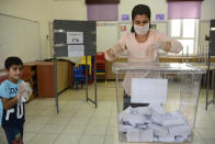 A woman casts her ballot at a polling station during Turkish Cypriots election for a new leader in the Turkish occupied area in the north part of the divided capital Nicosia, Cyprus, Sunday, Oct. 18, 2020. Turkish Cypriots vote to choose a leader who'll explore, with rival Greek Cypriots, whether there's enough common ground left for a deal to end the island's decades of ethnic division. (AP Photo/Nedim Enginsoy)