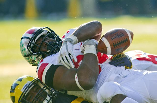 Ohio State running back Carlos Hyde fumbles the ball as he is tackled by Michigan safety Thomas Gordon, bottom, in the fourth quarter of an NCAA college football game in Ann Arbor, Mich., Saturday, Nov. 30, 2013. Ohio State won 42-41. (AP Photo/Tony Ding)