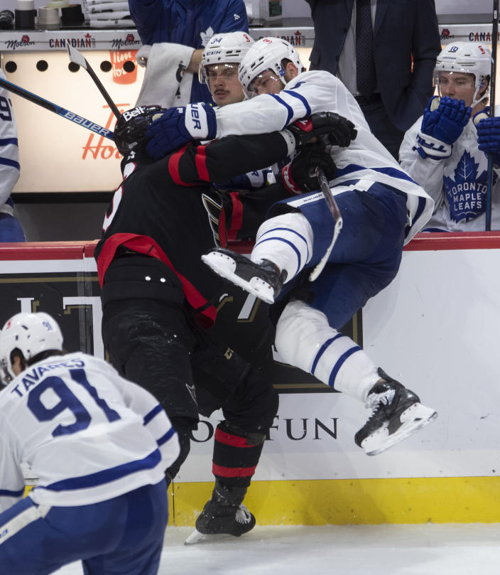Ottawa Senators left wing Austin Watson collides with Toronto Maple Leafs defenseman Jake Muzzin along the boards during the third period of an NHL hockey game in Ottawa, Ontario, Saturday, Jan. 16, 2021. (Adrian Wyld/The Canadian Press via AP)